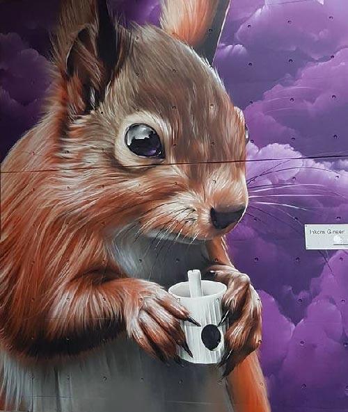 Esta imagen muestra el mural de un graffiti naturaleza donde el protagonista es una ardilla, está realizado en Madrid