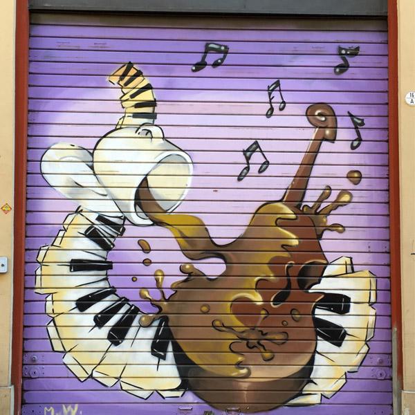 En la imagen vemos una persiana o cierre decorada por pintores de graffiti profesinales, es una escuela de música situada en Madrid, donde se utilizaron colores vivo e impactantes